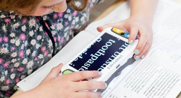 Une jeunne fille lit son cours avec la CANDY 5 HD II
