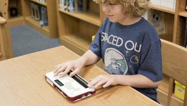 un jeune étudiant avec le Bloc note Braille Sense U2 Perkins
