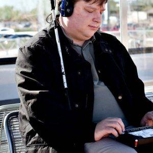 un homme assis dehors avec un Braille Sense U2 Perkins