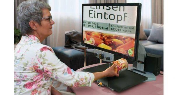 une femme lit une boite de conserve avec le téléagrandisseur parlant VEOVOX